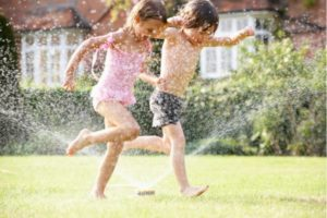 two kids running through the sprinklers