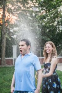 woman spraying a man with a hose