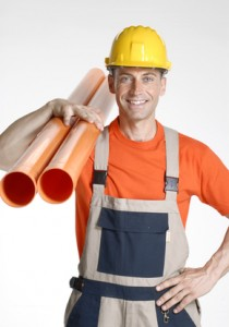 Construction worker holding pipes