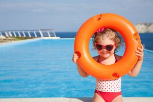 Little girl holding a pool float and standing near a pool
