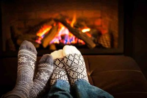 Two people's feet warming up by the fire