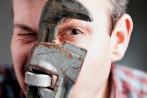 Man holding a wrench to his face