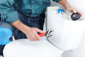 Plumber fixing a toilet that keeps running