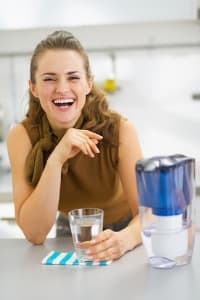 Woman smiling next to a water filtration pitcher